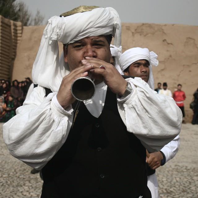 نگاره:  Man plays folk music of Khorasan, Iran, at the backyard of the tomb of Ferdowsi, beside the ruins of the ancient city of Tus. Playing this kind of music has become limited to cultural heritage and tourism exhibitions.